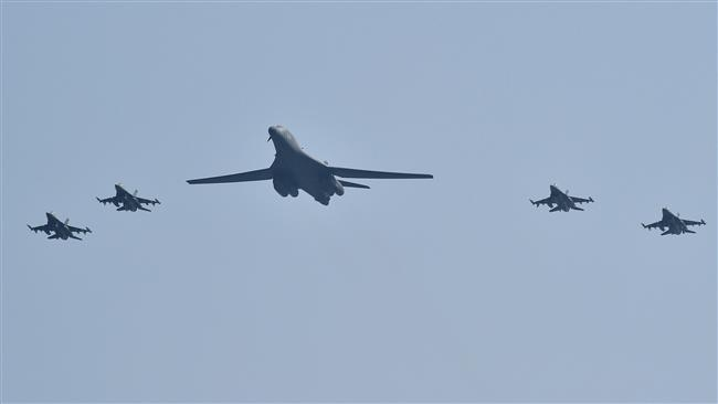 A US B1B Lancer is escorted by US F 16 fighter jets as it flies over the Osan Air Base Pyeongtaek