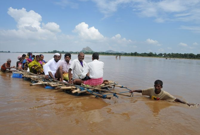 Villagers on a raft wade through the flooded river in Gaya In Bihar