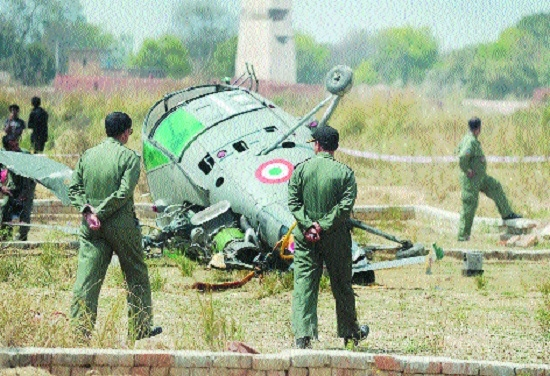 IAF personnel walk next to a Chetak helicopter that crashed