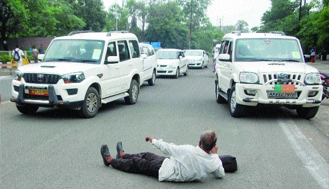 Dejected farmer lies down before MLA vehicle