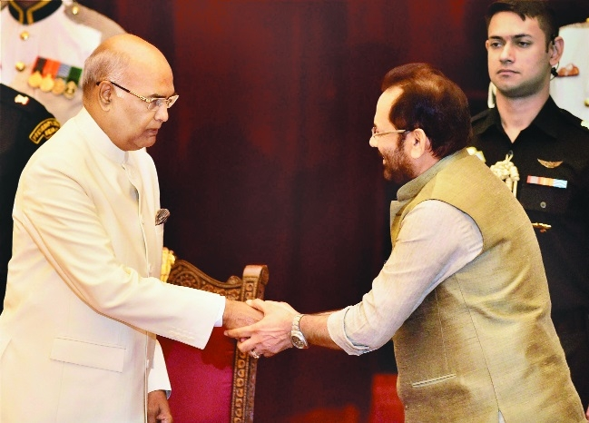 President Nath Kovind shakes hands with new Cabinet Minister Mukhtar Abbas Naqvi