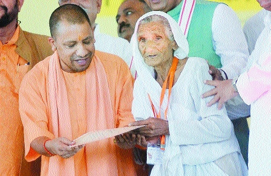 CM Yogi Adityanath gives a certificate to a farmer to clear her loans