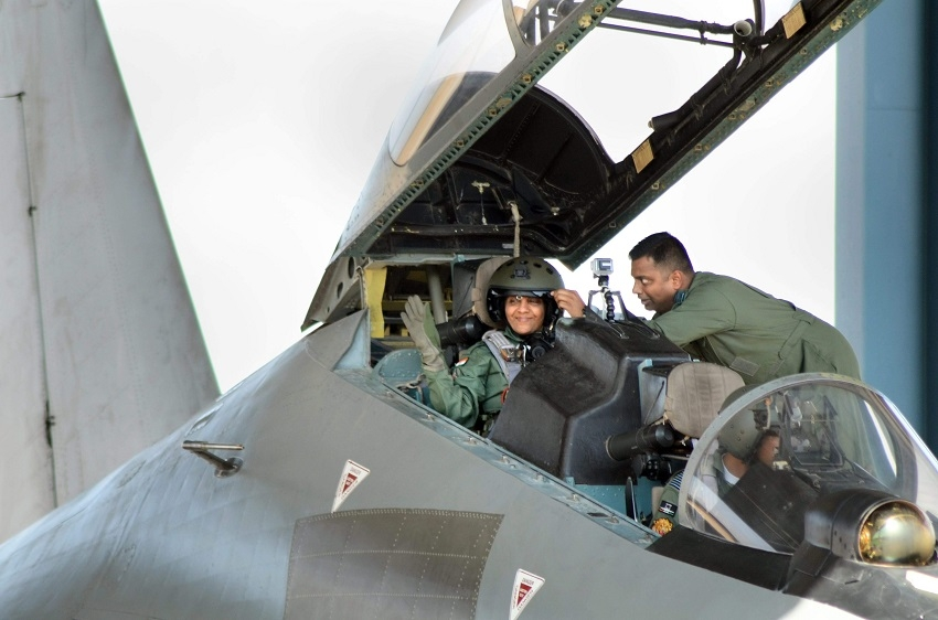 D M Nirmala Sitharaman waves from the cock pit of IAFs Sukhoi 30 MKI plane as an IAF personnel adjusts her helmet before taking off for a sortie in Jodhpur