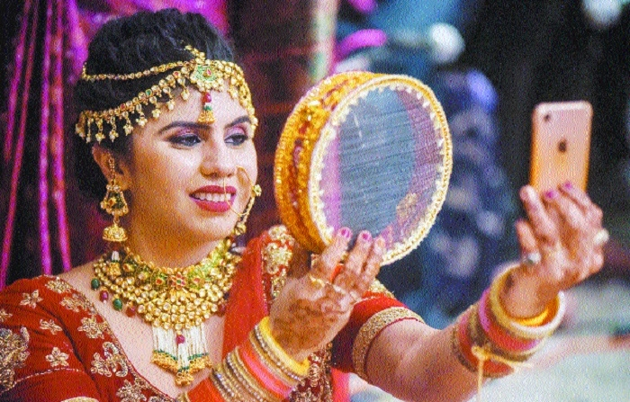 A woman takes selfie by using her cell phone on Karwa Chauth in Indore M P