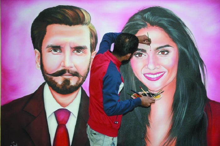 Artist Jagjot Singh Rubal gives final touches to a painting of couple Deepika Padukone and actor Ranveer Singh which he will present to them as a wedding gift in Amritsar on Tuesday