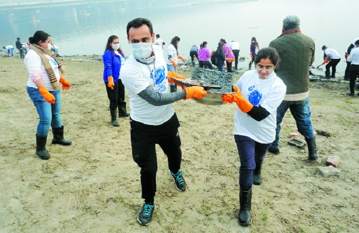 Employees of a company take part in a Yamuna Clean programme at Yamuna Chhath Ghat
