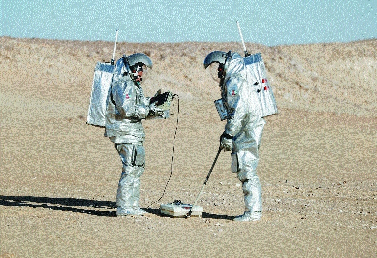 Members of the AMADEE18 Mars simulation mission wear spacesuits while conducting scientific experiments during an analog field simulation in Omans