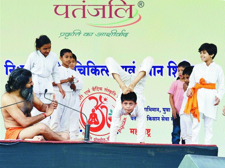 A child performs as Yoga guru Swami Ramdev claps during a yoga camp in Karad Maharashtra on Sunday