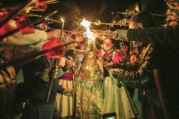 Macedonian Orthodox worshipers light candles from the holy fire that arrived from Jerusalem during the Easter service at the St Jovan Bigorski monastery