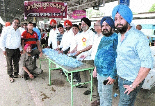Giants Group members distribute water pouches at railway station