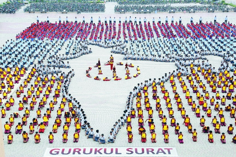 Schoolchildren sit in formation as they depict Indias map during a yoga rehearsal in Surat on the eve of International Yoga Day at Shree Swaminarayan Gurukul Vedroad Surat on Wednesday