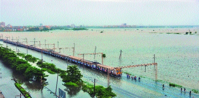 Commuters stranded on their way to Mumbai as a section of Western Railway remain suspended due to waterlogging on tracks after heavy rainfall at Nallasopara area in Mumbai