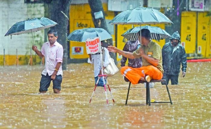 A municipal employee warns pedestrians about an open manhole as water floods the streets rainfall in Mumbai