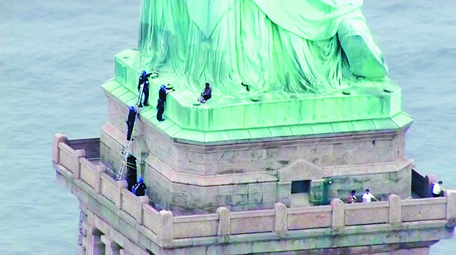 Woman climbs base of Statue of Liberty to protest Trump's immigration policy