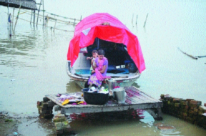 A woman and a boy sit on a boat with their belongings before moving to drier ground after flooding on the banks of Ganga at Sangam area in Allahabad